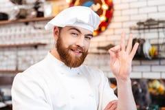 Cozinheiro alegre do cozinheiro chefe que mostra o sinal aprovado na cozinha Imagem de Stock