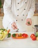 Cozinheiro chefe Adding Parsley a uma pimenta enchida foto de stock royalty free