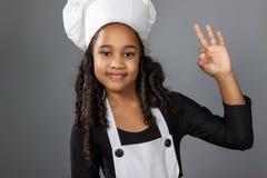 Cozinheiro chefe alegre da menina que mostra o sinal aprovado Imagens de Stock Royalty Free