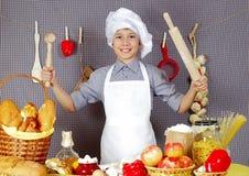 Cozinheiro chefe alegre na tabela com produtos diferentes fotografia de stock