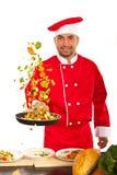 Cozinheiro chefe alegre que lanç vegetais Fotografia de Stock Royalty Free