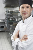 Cozinheiro chefe With Arms Crossed na cozinha fotografia de stock royalty free