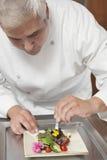 Cozinheiro chefe Arranging Edible Flowers na salada Fotografia de Stock Royalty Free