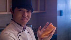 Cozinheiro chefe asiático de sorriso que está na cozinha filme
