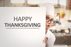 Cozinheiro chefe asiático novo da mulher que guarda a bandeira branca com Thanksgiv feliz Fotos de Stock
