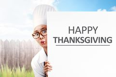 Cozinheiro chefe asiático novo da mulher que guarda a bandeira branca com Thanksgiv feliz Imagens de Stock