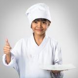 Cozinheiro chefe asiático pequeno da menina que mostra a placa branca vazia Fotografia de Stock