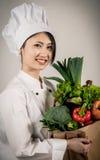Cozinheiro chefe asiático fêmea com o saco de papel de vegetais Imagens de Stock Royalty Free