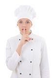 Cozinheiro chefe atrativo novo da mulher que mostra o sinal do silêncio isolado no whi imagens de stock royalty free