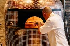 Cozinheiro chefe Baking Caprese Bianca Pizza dentro do forno ardente de madeira da pizza imagens de stock