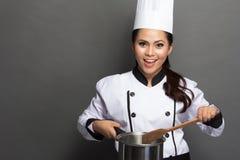 Cozinheiro chefe bonito da mulher na ação Fotografia de Stock
