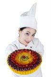Cozinheiro chefe bonito da mulher que guarda um bolo Imagem de Stock Royalty Free