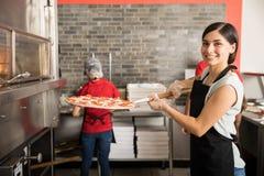 Cozinheiro chefe bonito da mulher que põe a pizza feita fresca no forno imagens de stock