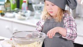 Cozinheiro chefe bonito pequeno da menina que prepara-se para peneirar a farinha através de uma peneira filme
