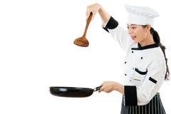 Cozinheiro chefe bonito que guarda uma espátula de madeira foto de stock royalty free