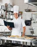 Cozinheiro chefe With Book Standing pelo contador de cozinha Fotos de Stock Royalty Free
