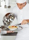 Cozinheiro chefe Checking Pasta Dish com Tong Foto de Stock Royalty Free