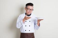 Cozinheiro chefe chinês asiático maduro que apresenta o prato Imagens de Stock