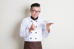 Cozinheiro chefe chinês asiático maduro que apresenta o prato e o polegar acima Imagem de Stock