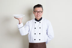 Cozinheiro chefe chinês asiático maduro que guarda um prato Imagem de Stock
