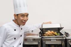 Cozinheiro chefe chinês que mostra o alimento Imagens de Stock Royalty Free