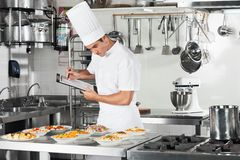 Cozinheiro chefe With Clipboard Going com do cozimento Foto de Stock Royalty Free