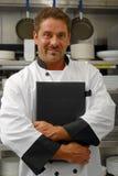 Cozinheiro chefe com menu Fotografia de Stock Royalty Free