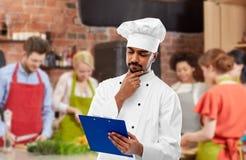 Cozinheiro chefe com menu na prancheta na aula de culinária fotografia de stock royalty free