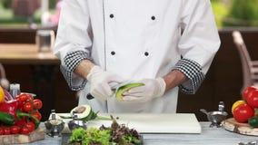 Cozinheiro chefe com o abacate da casca da faca vídeos de arquivo
