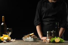 Cozinheiro chefe com ostras frescas e uma garrafa do vinho seco branco em um fundo escuro, foto horizontal, para a propaganda do  foto de stock