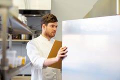 Cozinheiro chefe com a prancheta que faz o inventário na cozinha fotografia de stock