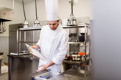Cozinheiro chefe com a prancheta que faz o inventário na cozinha imagem de stock