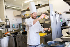 Cozinheiro chefe com a prancheta que faz o inventário na cozinha foto de stock royalty free