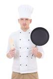 Cozinheiro chefe considerável novo do homem no uniforme com a frigideira isolada em w Imagens de Stock