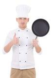 Cozinheiro chefe considerável novo do homem no uniforme com os polegares da frigideira do Teflon Imagens de Stock