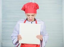 Cozinheiro chefe da mulher que cozinha o alimento Conceito culinário O cozinheiro amador leu receitas do livro A menina aprende a fotos de stock