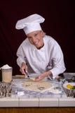 Cozinheiro chefe da pastelaria que levanta a massa de pão cortada Foto de Stock