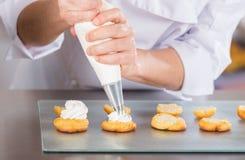Cozinheiro chefe de pastelaria com profiteroles imagem de stock royalty free