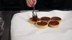 Cozinheiro chefe de pastelaria da jovem mulher que faz a sobremesa em sua própria cozinha Tartles cozidos de enchimento com creme vídeos de arquivo