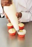 Cozinheiro chefe de pastelaria que aplica a geada aos queques com saco tranquilo Fotografia de Stock Royalty Free