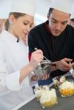 Cozinheiro chefe de pastelaria que dá o estudante que cozinha o conselho Imagens de Stock
