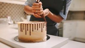 Cozinheiro chefe de pastelaria que decora um bolo fotos de stock royalty free