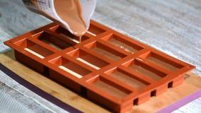 Cozinheiro chefe de pastelaria que enche um molde do silicone com uma musse de chocolate Fazendo a sobremesa francesa filme