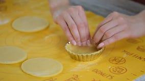 Cozinheiro chefe de pastelaria que faz os tartlets, pondo a massa em pratos de cozimento filme