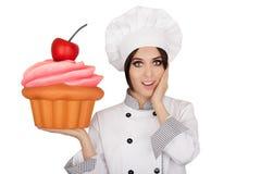 Cozinheiro chefe de pastelaria surpreendido Holding Huge Cupcake da mulher fotografia de stock