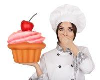 Cozinheiro chefe de pastelaria surpreendido Holding Huge Cupcake da mulher fotografia de stock royalty free