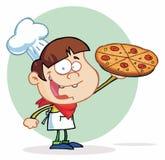 Cozinheiro chefe de sorriso do menino que mostra uma pizza deliciosa Imagens de Stock Royalty Free