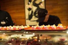 Cozinheiro chefe de sushi no fundo borrado trabalho Imagem de Stock Royalty Free