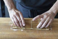 Cozinheiro chefe de sushi que rola acima do sushi em uma esteira fotografia de stock
