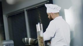 Cozinheiro chefe do homem que cozinha no frigideira chinesa na cozinha Cozinheiro chefe focalizado que prepara o alimento asiátic filme
